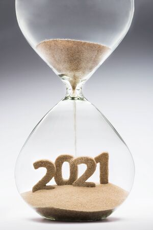 Concepto de año nuevo 2021 con arena cayendo de reloj de arena tomando la forma de un 2021