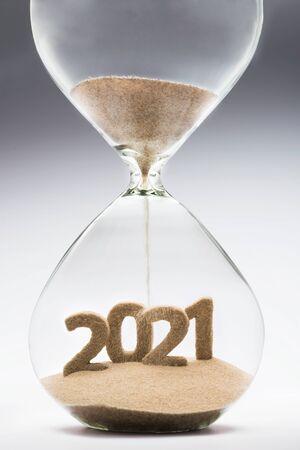 Concetto di Capodanno 2021 con sabbia che cade a clessidra che assume la forma di un 2021