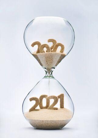 Concetto di Capodanno 2021 con sabbia che cade a clessidra che assume la forma di un 2021 Archivio Fotografico