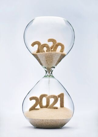 New Year 2021 concept with hourglass falling sand taking the shape of a 2021 스톡 콘텐츠 - 129449499