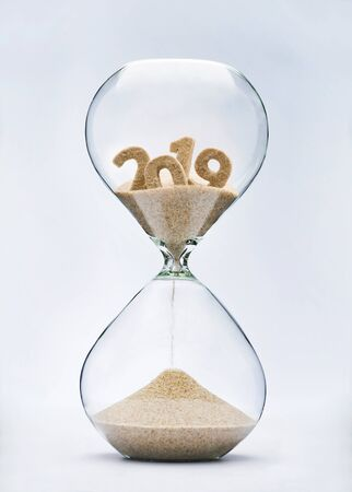 New Year 2020 concept. Time running out concept with hourglass falling sand from 2019. Фото со стока