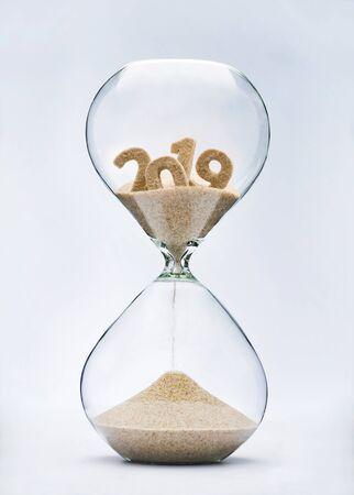 Notion de nouvel an 2020. Concept de temps qui s'écoule avec du sable tombant en sablier à partir de 2019.