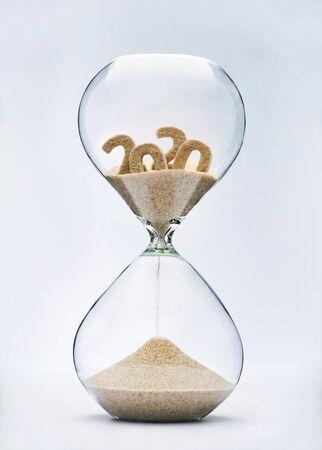 Concetto di Capodanno 2021. Il tempo sta per scadere con la sabbia che cade a clessidra dal 2020.