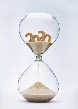 New Year 2021 concept. Time running out concept with hourglass falling sand from 2020. 免版税图像