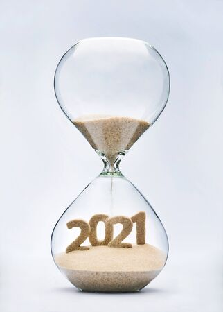 New Year 2021 concept with hourglass falling sand taking the shape of a 2021 Фото со стока
