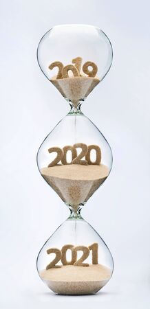 Past, present and future concept. 3 part hourglass. Falling sand taking the shape of years 2019, 2020 and 2021.