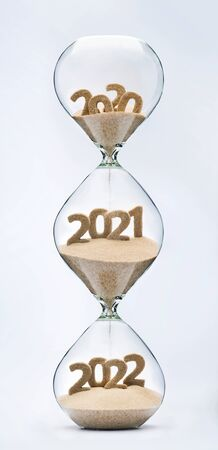 Past, present and future concept. 3 part hourglass. Falling sand taking the shape of years 2020, 2021 and 2022.
