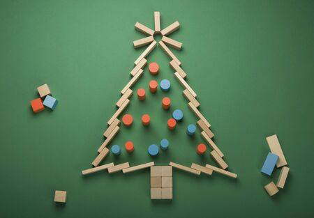 Christmas tree made out of arrangement of toy wooden cubes with colourful lights