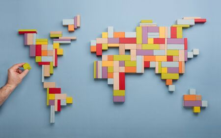 Top view on man's hand building world global map with colorful wooden bricks. World unity, diversity and education concept. Фото со стока