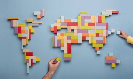 Top view on child's and father's hands playing with colorful wooden bricks building world global map. World unity, diversity, family and education concept.