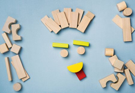 Emotions and emoticons faces. Happy, sad, smiling, worried, curious and angry faces emoticons made up of toy wooden building blocks.