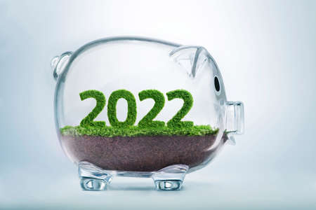 2022 is a good year for business. Grass growing in the shape of year 2022, inside a transparent piggy bank.