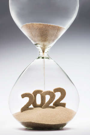 New Year 2022 concept with hourglass falling sand taking the shape of a 2022