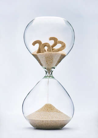 New Year 2023 concept. Time running out concept with hourglass falling sand from 2022.