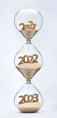 Past, present and future concept. 3 part hourglass. Falling sand taking the shape of years 2021, 2022 and 2023. Фото со стока