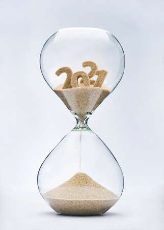 New Year 2022 concept. Time running out concept with hourglass falling sand from 2021. Фото со стока