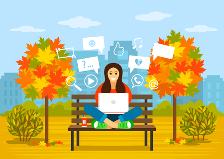 A beautiful young girl is sitting in a park in autumn with a laptop for searching information on the Internet. concept of modern man and communication, learning online.