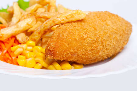 Chicken Kiev with corn and french fries photo