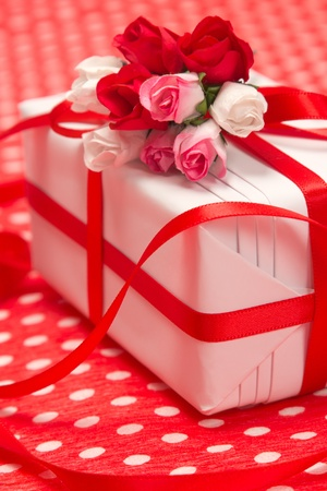 felicitation: White gift box with red bow and paper flowers on red background