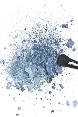 Crushed blue eyeshadow with makeup brush on white background photo