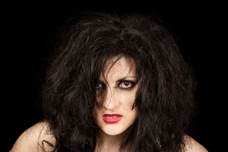 disheveled: Portrait of black-haired woman with disheveled hair and ruby lipstick on black background Stock Photo