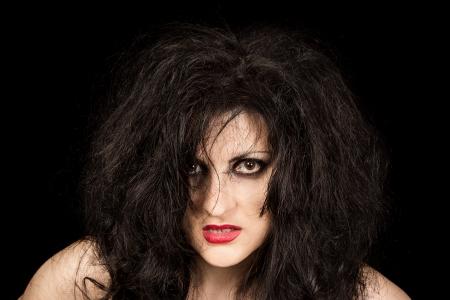 beldam: Ritratto di donna dai capelli neri, con i capelli arruffati e rossetto rubino su sfondo nero