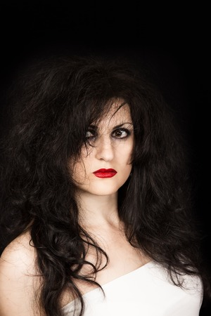 beldam: Ritratto di donna dai capelli neri, con i capelli arruffati, gli occhi pazzi e labbra rubino su sfondo nero