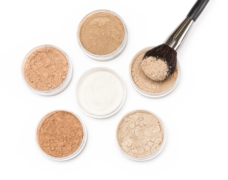 Makeup brush with jars filled with loose cosmetic powder different tones
