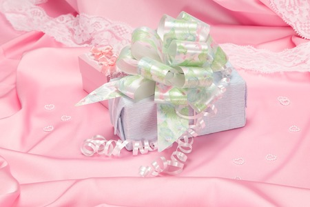 felicitation: Blue gift box decorated with big bow on pink silk fabric with small hearts made of beads
