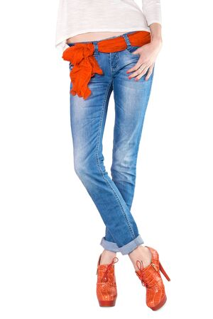 Shapely female legs in blue jeans with a scarf as a belt and orange boots with high heels on white background