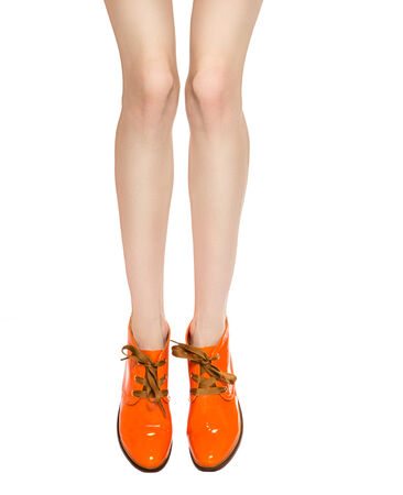 trotters: Shapely female legs in orange laced boots isolated on white