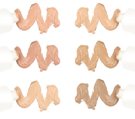 Different tones of foundation squeezed out from tube on white background