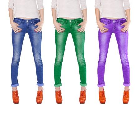 Welgevormde vrouwelijke benen gekleed in blauw, groen en violet jeans