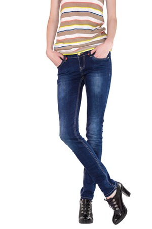 Shapely female legs dressed in dark blue jeans, striped shirt and black varnished boots on white background