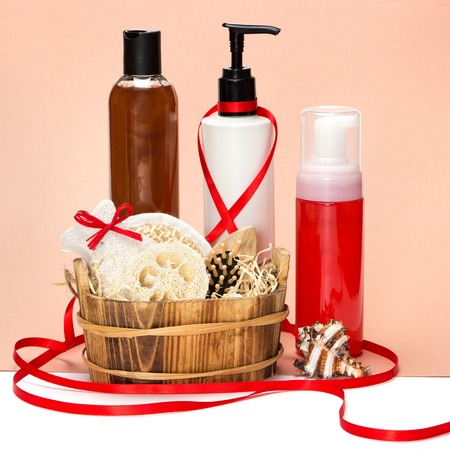 Cosmetics as a gift: composition with different cosmetic products for body care, spa accessories in wooden basket, ribbon and bow photo