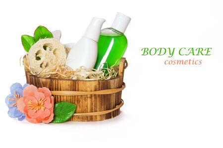 Jars with body care cosmetics in wooden basket and flowers on white background