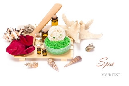 Spa accessories: sea salt with loofah, rose petals on the wooden spoon and bottles filled with aromatic oils on white background photo