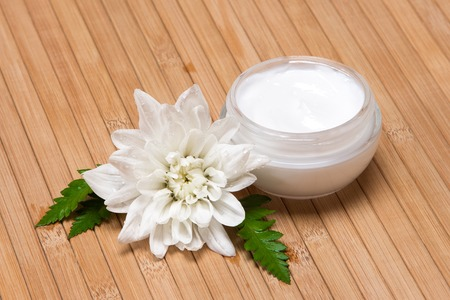 Natural moisturizing face cream concept: open jar of cream with wet white flower and fern leaves on wooden surface photo
