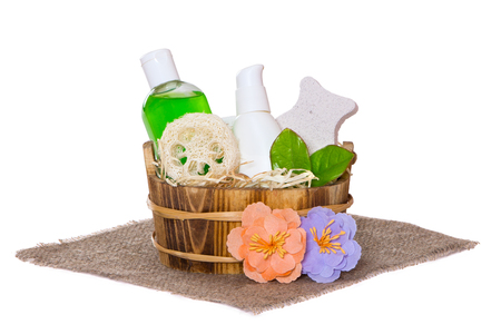 Jars with body care cosmetics in wooden basket and flowers on hessian cloth napkin, white