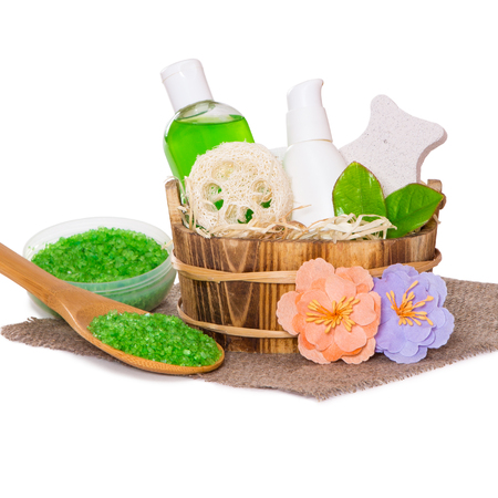 Jars with body care cosmetics in wooden basket, sea salt in wooden spoon and flowers on hessian cloth napkin, white  Stock Photo