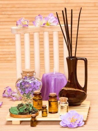 incense sticks: Aromatherapy accessories: floral petals, bottles filled with aromatic oils, incense sticks, candle on wooden surface