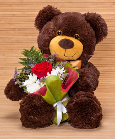 Smiling teddy bear holding beautiful floral bouquet in paws photo