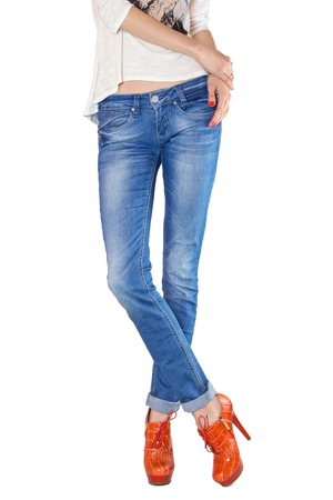 shapely legs: Shapely female legs dressed in blue jeans and orange boots with high heels on white background Stock Photo