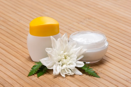 Natural moisturizing face cream concept: jars of cream with wet white flower and fern leaves on wooden surface photo