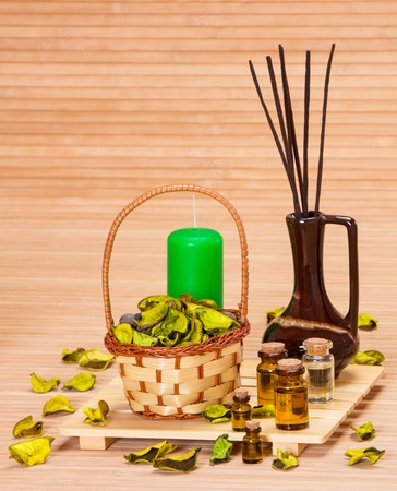 incense sticks: Aromatherapy accessories: floral petals in wicker basket, bottles filled with aromatic oils, incense sticks, candle on wooden surface