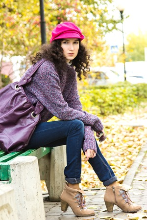 Young stylish woman dressed in oversized knitted sweater, skinny jeans, peaked cap and heels with big bag sitting on bench in city park. Fashion beautiful girl photo