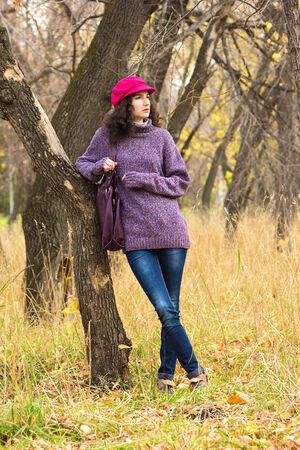 skinny jeans: Joven y elegante vestido con jersey de punto de gran tama�o, jeans ajustados, enarbolaron el casquillo con el bolso grande en el parque de la ciudad. Moda hermosa ni�a