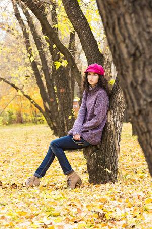 skinny jeans: Joven y elegante vestido con jersey de punto de gran tama�o, jeans ajustados, casquillo enarbolado y tacones que tienen descanso en el Parque de la ciudad. Moda hermosa ni�a