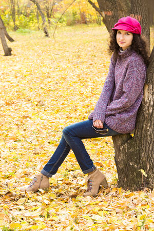 oversize: Young stylish smiling woman dressed in oversized knitted sweater, skinny jeans, peaked cap and heels having rest in city park. Fashion beautiful girl