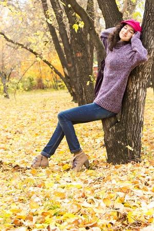 skinny jeans: Mujer sonriente con estilo joven vestido con su�ter de punto de gran tama�o, jeans ajustados, alcanz� su punto m�ximo gorra y zapatos de tac�n que tienen resto en parque de la ciudad. Moda hermosa ni�a Foto de archivo